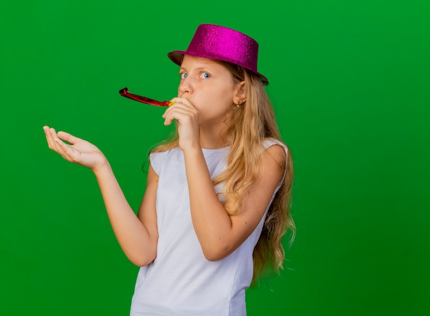 생일 축하 휘파람을 불고 휴가 모자에 예쁜 소녀