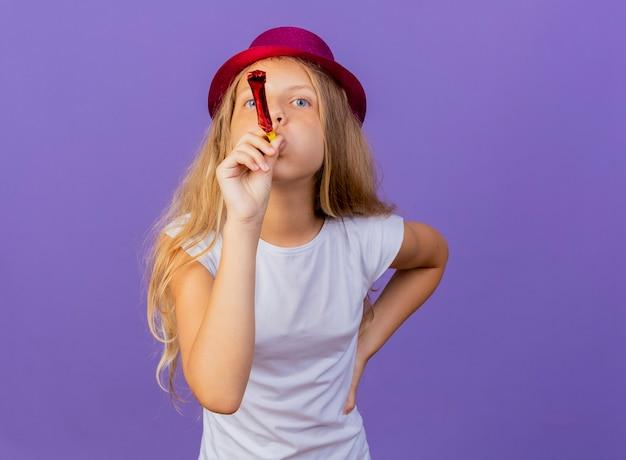 보라색 배경 위에 서 행복하고 긍정적 인 휘파람을 불고 휴가 모자에 예쁜 소녀, 생일 파티 개념