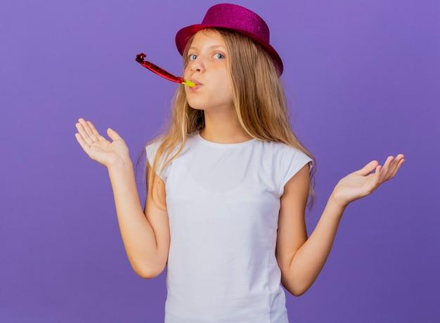 보라색 배경 위에 서있는 혼란, 생일 파티 개념을 찾고 휘파람을 불고 휴가 모자에 예쁜 소녀