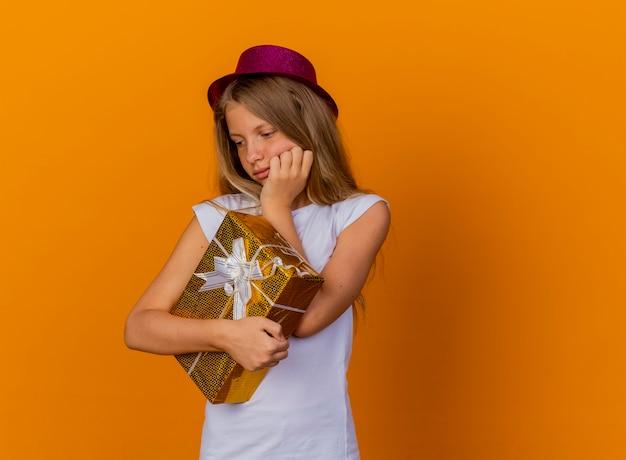 Симпатичная маленькая девочка в праздничной шляпе, держащая подарочную коробку, смотрит в сторону с задумчивым выражением лица, концепция вечеринки по случаю дня рождения стоит на оранжевом фоне