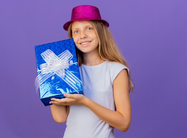 Симпатичная маленькая девочка в праздничной шляпе, держащей подарочную коробку, смотрящую в камеру со счастливым улыбающимся лицом, концепция вечеринки по случаю дня рождения, стоящая на фиолетовом фоне