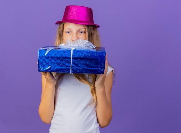Симпатичная маленькая девочка в праздничной шляпе держит подарочную коробку, заинтригованная, глядя на нее, концепция вечеринки по случаю дня рождения стоит на фиолетовом фоне