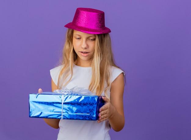 Милая маленькая девочка в праздничной шляпе держит подарочную коробку, глядя на нее с удивлением, концепция вечеринки по случаю дня рождения стоит на фиолетовом фоне