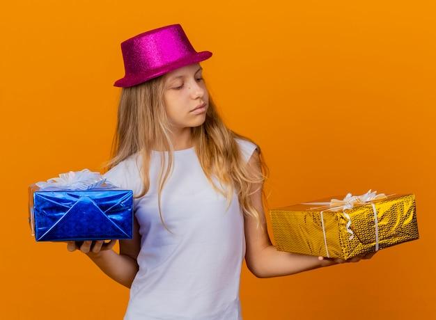 Милая маленькая девочка в праздничной шляпе, держащей подарочные коробки