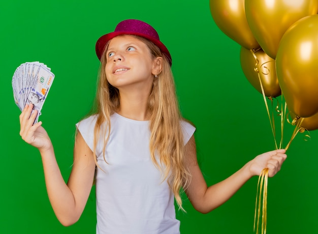 お金を保持している休日の帽子のかわいい女の子