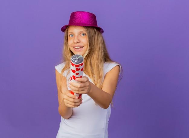 파티 크래커 행복 하 고 흥분, 보라색 배경 위에 서있는 생일 파티 개념을 들고 휴가 모자에 예쁜 소녀