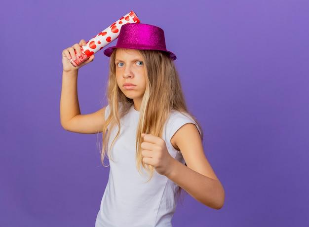 성난 얼굴 떨림 주먹으로 카메라를보고 파티 크래커를 들고 휴가 모자에 예쁜 소녀, 보라색 배경 위에 서있는 생일 파티 개념