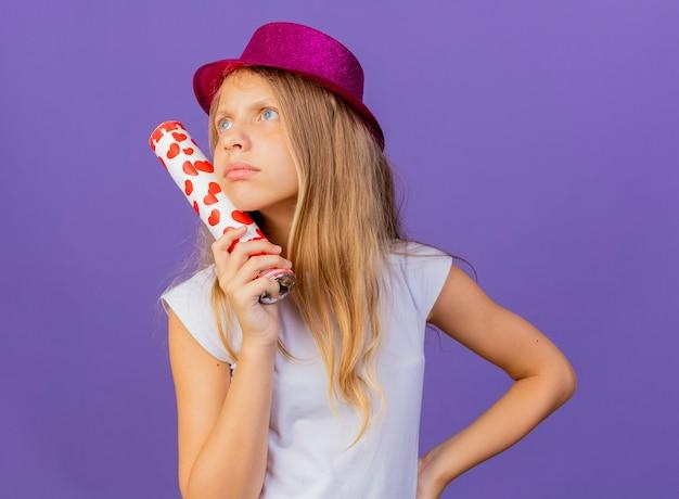 보라색 배경 위에 서 의아해, 생일 파티 개념을 찾고 파티 크래커를 들고 휴가 모자에 예쁜 소녀