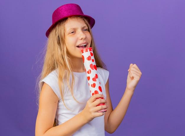 마이크 노래로 사용하는 파티 크래커를 들고 휴가 모자에 예쁜 소녀, 보라색 배경 위에 서있는 생일 파티 개념