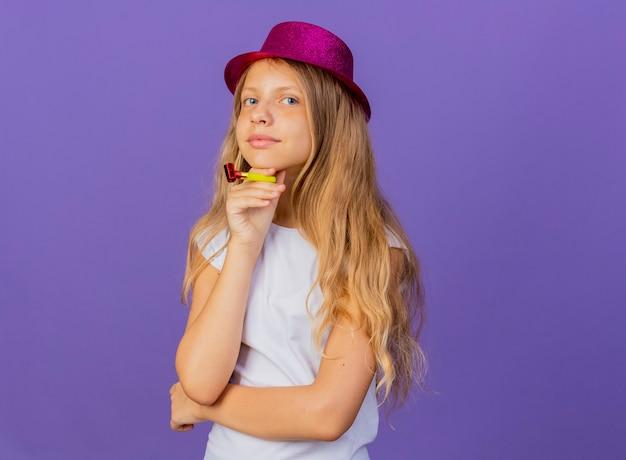 행복 한 얼굴, 보라색 배경 위에 서 생일 파티 개념으로 웃 고 카메라를보고 휘파람을 들고 휴가 모자에 예쁜 소녀