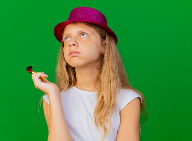 困惑して脇を探している休日の帽子のかわいい女の子