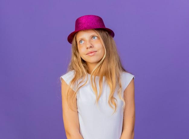 顔に笑顔で脇を見て、紫色の背景の上に立っている誕生日パーティーのコンセプトの休日の帽子のかわいい女の子