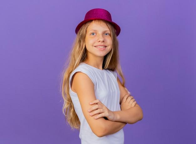 胸に交差した手、紫色の背景の上に立っている誕生日パーティーのコンセプトに笑顔で脇を見てホリデー帽子のかわいい女の子