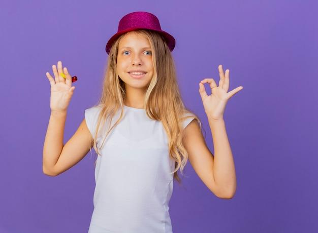 휴가 모자에 예쁜 소녀 확인 서명, 보라색 배경 위에 서있는 생일 파티 개념을 보여주는 미소 카메라를보고
