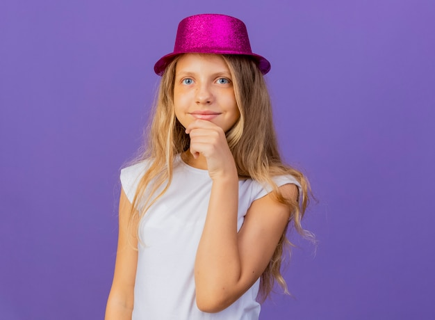 턱에 손으로 웃 고 카메라를 찾고 휴가 모자에 예쁜 소녀, 보라색 배경 위에 서 생일 파티 개념