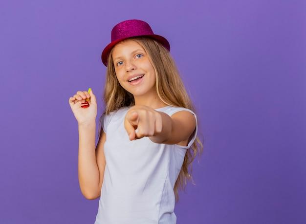보라색 배경 위에 서 행복하고 긍정적 인, 생일 파티 개념 미소 카메라에 검지 손가락으로 가리키는 휴가 모자에 예쁜 소녀