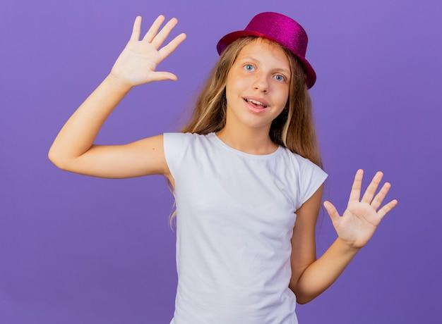 휴가 모자에 예쁜 소녀 손바닥 행복하고 긍정적 인 미소, 보라색 배경 위에 서있는 생일 파티 개념