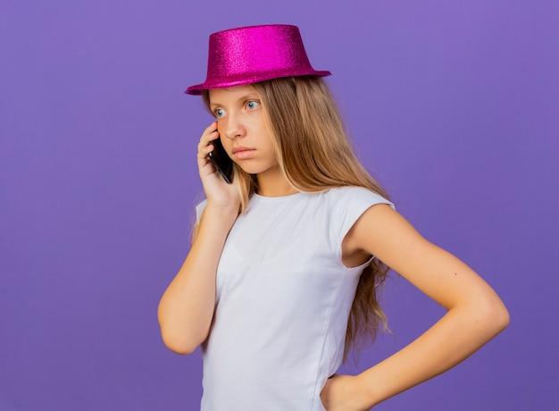 보라색 배경 위에 서있는 혼란스러운 휴대 전화에 휴가 모자에 예쁜 소녀, 생일 파티 개념 서