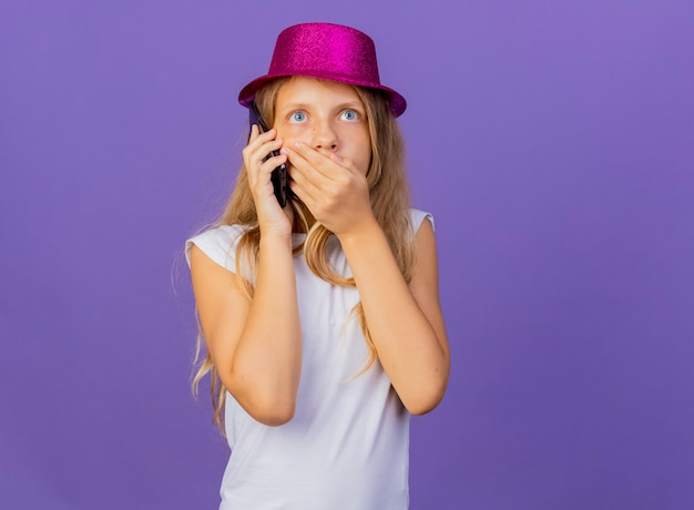 보라색 배경 위에 서있는 충격을 받고 휴대 전화에 휴가 모자에 예쁜 소녀, 생일 파티 개념 서