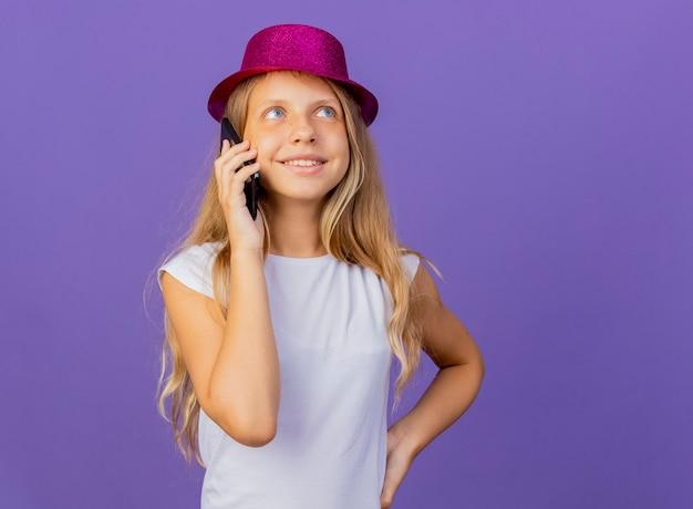 웃 고, 보라색 배경 위에 서있는 생일 파티 개념 휴대 전화에 얘기하는 휴가 모자에 예쁜 소녀