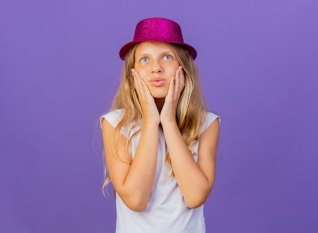 보라색 배경 위에 서있는 긍정적 인 감정을 느끼고 그녀의 뺨을 만지고 휴가 모자에 예쁜 소녀, 생일 파티 개념