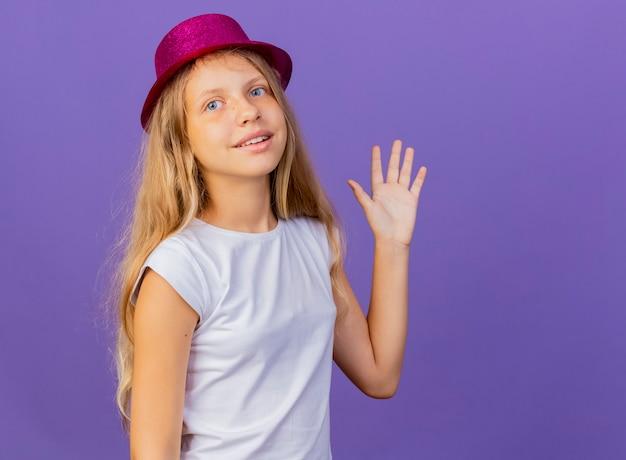웃 고 손으로 흔들며 휴가 모자에 예쁜 소녀, 보라색 배경 위에 생일 파티 개념 서