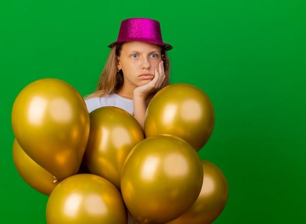 옆으로 의아해 보이는 baloons의 무리와 함께 휴가 모자에 예쁜 소녀, 녹색 배경 위에 서 생일 파티 개념