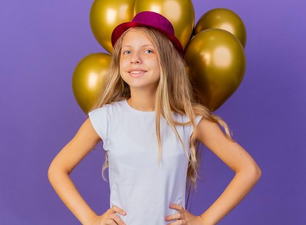 쾌활하게 웃는 카메라를 찾고 baloons의 무리와 함께 휴가 모자에 예쁜 소녀, 보라색 배경 위에 생일 파티 개념 서