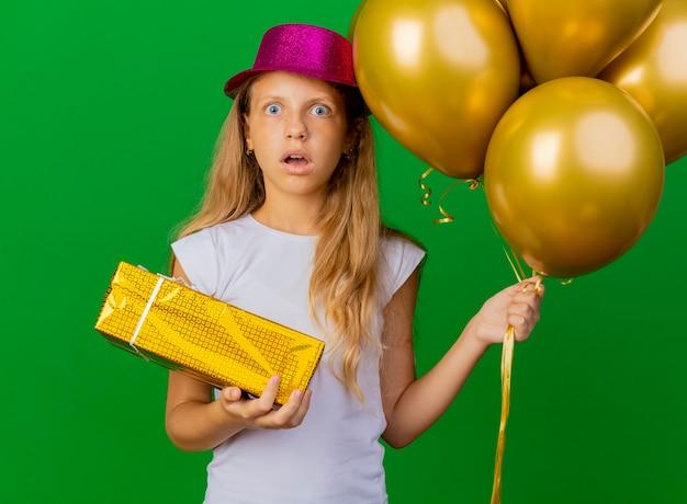 Милая маленькая девочка в праздничной шляпе с кучей воздушных шаров