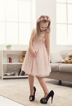 ママの靴を履いたかわいい女の子。自宅でハイヒールを履こうとしている小さなファッショニスタ、コピースペース