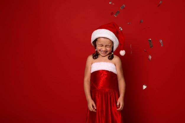 サンタのカーニバルの服装のかわいい女の子は、目を閉じてポーズをとって、スパンコールと紙吹雪が落ちる赤い背景に対してかわいい笑顔を喜んでいます。クリスマス、新年のお祝いのコンセプト、コピースペース