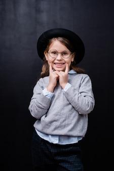 カメラの前に立っている間歯を見せる笑顔であなたを見ているスマートなカジュアルウェアと眼鏡のかわいい女の子