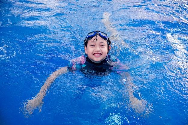 미소와 여름에 행복 수영장에서 예쁜 소녀