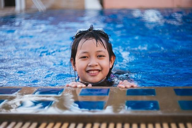 Довольно маленькая девочка в бассейне с улыбкой и счастливой