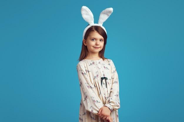 Симпатичная маленькая девочка в белой рубашке и кроличьих ушах очаровательно позирует на синем