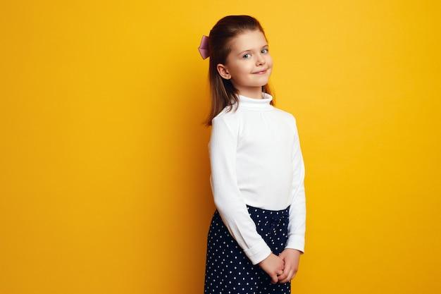 Милая маленькая девочка в белой водолазке очаровательно позирует на желтом фоне Premium Фотографии