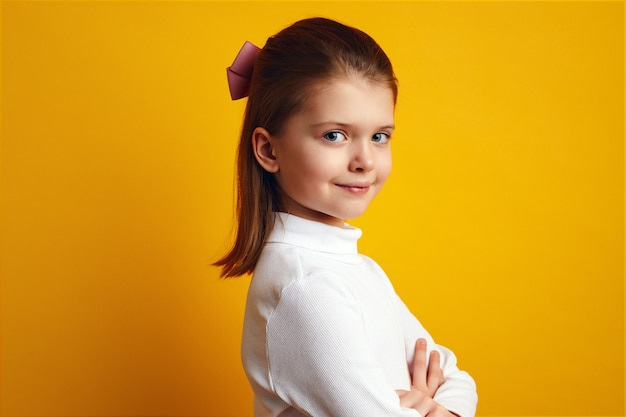 Милая маленькая девочка в белой водолазке очаровательно позирует на желтом фоне