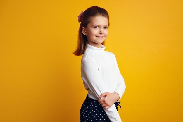 Симпатичная маленькая девочка в белой водолазке очаровательно позирует на желтой стене