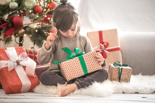 Хорошенькая девочка держит подарочную коробку и улыбается, сидя на кровати в своей комнате дома