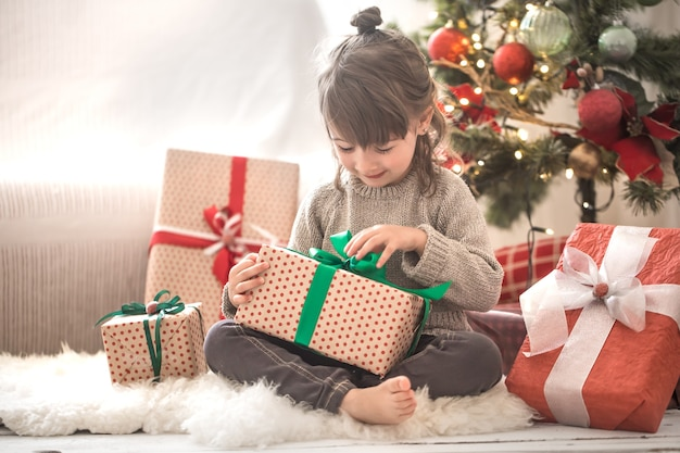 예쁜 소녀는 선물 상자를 들고 집에서 그녀의 방에있는 그녀의 침대에 앉아있는 동안 웃고 있습니다.