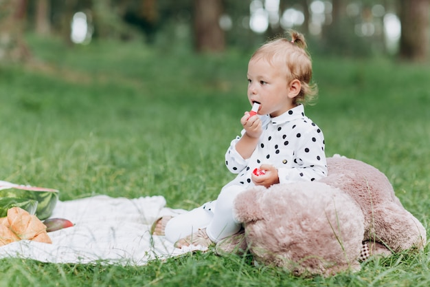 Pretty little girl is playing with teddy bear toy outdoors and doing make up with lipstick, cute child having fun in the park on picnic in summer time, happy childhood concept