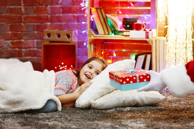 Pretty little girl laying on the pillow under soft plaid waiting for santa's gift in christmas decorated room