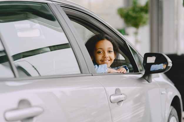 Pretty little girl looking from the car. child in a car salon.