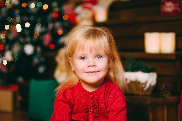 Довольно маленькая девочка смотрит в камеру с боке Premium Фотографии