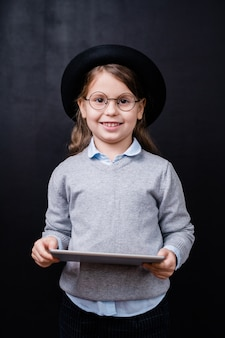 Pretty little girl looking at you with toothy smile while using touchpad in front of camera against black space