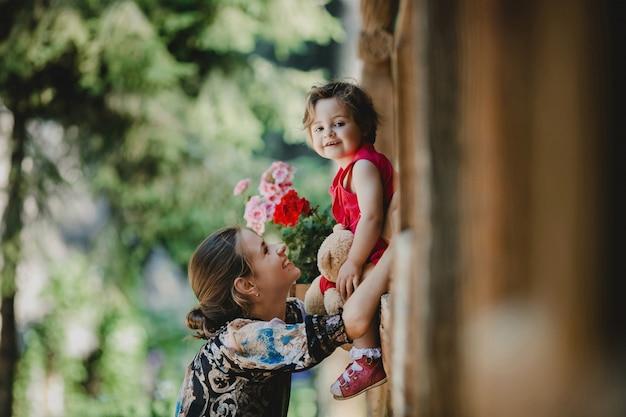 Маленькая девочка смотрит вниз, сидя на деревянном подоконнике