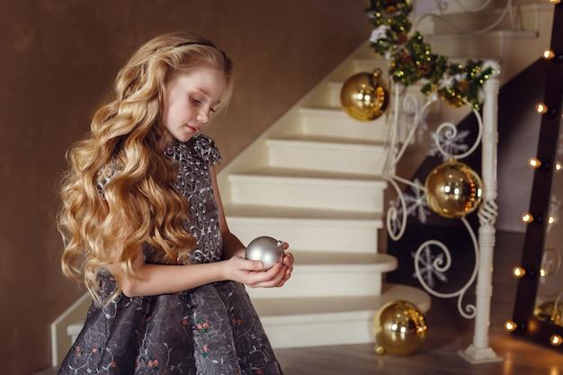 새 해 나무 근처 예쁜 소녀입니다. 휴가를 기다리는 크리스마스 트리 근처 드레스에서 아름 다운 소녀. 크리스마스 장식 인테리어.
