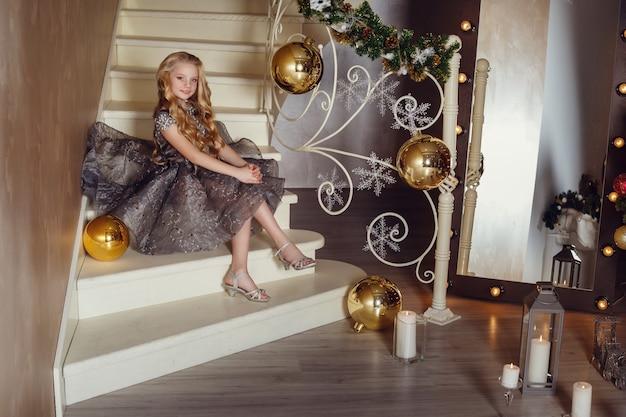 Милая маленькая девочка возле новогодней елки. красивая девушка в платье возле елки в ожидании праздника. интерьер с рождественскими украшениями.