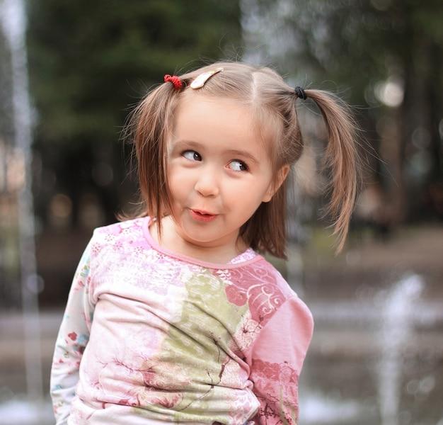 街の噴水の背景にかわいい女の子。