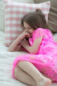 Pretty little girl in pink princess dress in bed with cushin